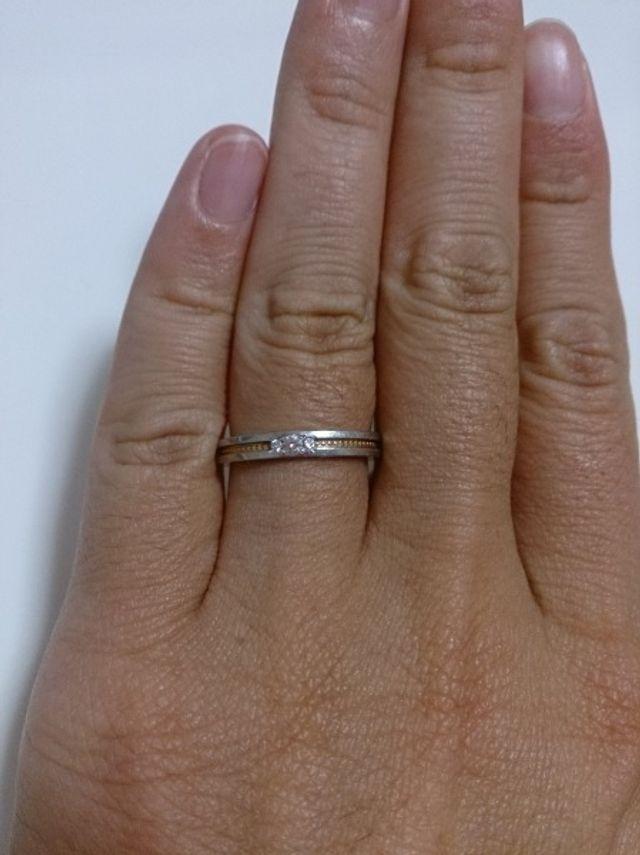 指にはめた結婚指輪の写真