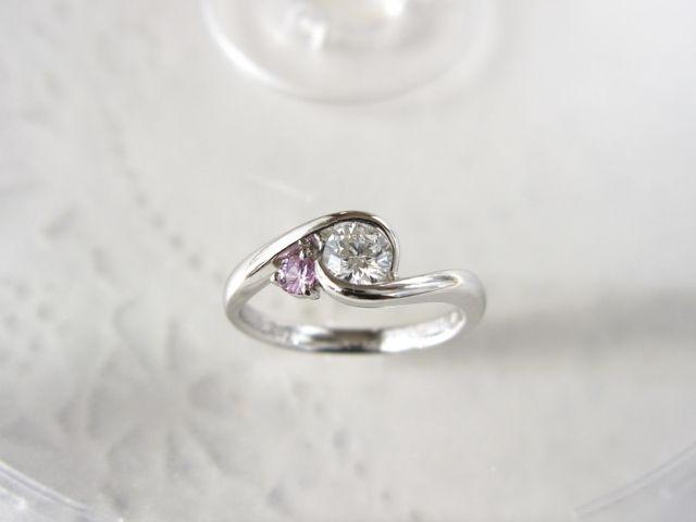 ダイヤを包み込みつつ、横に誕生石を添えるデザインにしました。